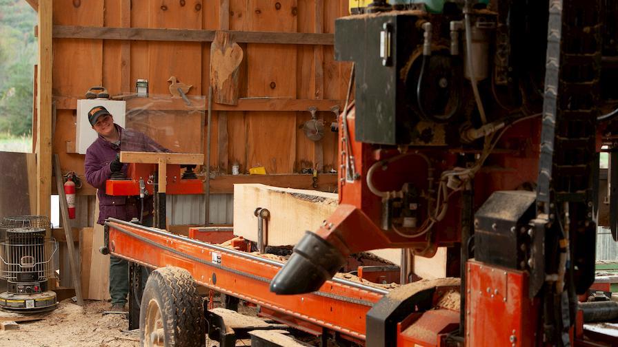 Megan sawing lumber on Wood-Mizer LT70 portable sawmill